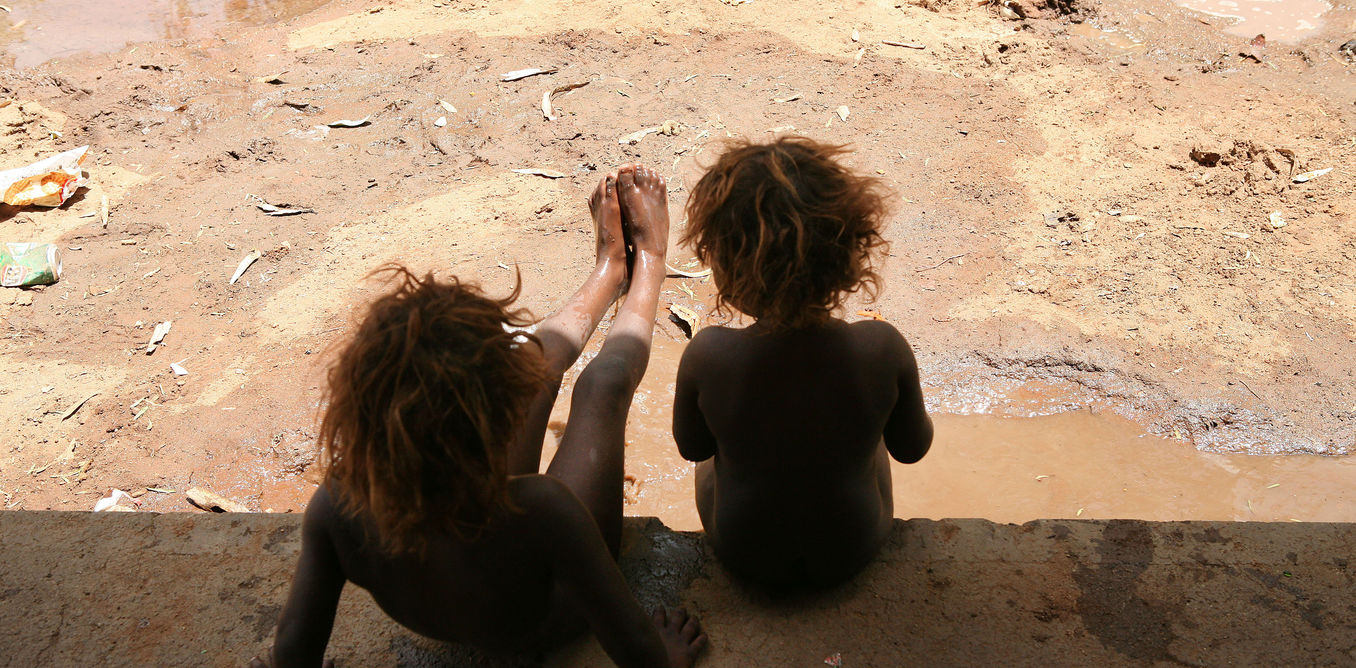 **FILE** An undated file image of sisters playing in the mud after a rare rain at Hoppy's 'town camp' on the outskirts of Alice Springs in the Northern Territory. Shocking claims of youth sexual abuse and prostitution involving indigenous children in far north Queensland communities have emerged in a government-commissioned report, Saturday, March 12, 2016. (AAP Image/Marianna Massey) NO ARCHIVING