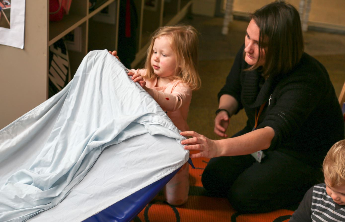 young child and educator prepare bedding